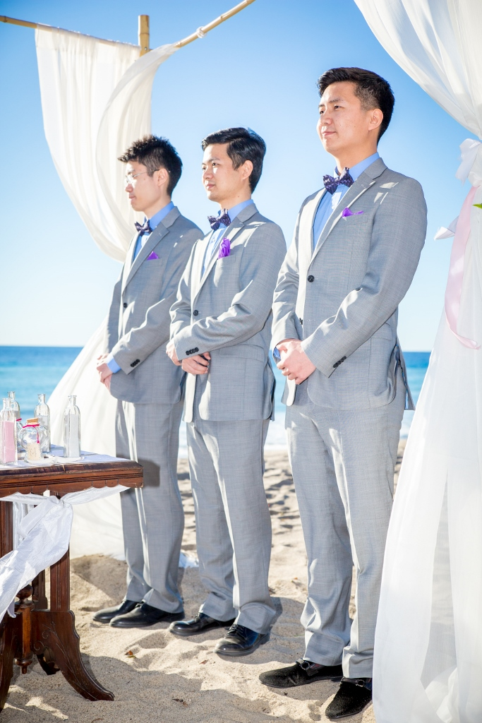 Grooms taking vows on the beach.jpg